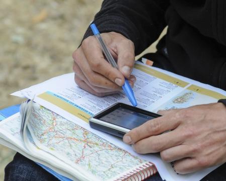 guia turistico: joven con un mapa y gps para planificar una ruta mediante un mapa, gps, y gu�a para planificar un viaje Foto de archivo