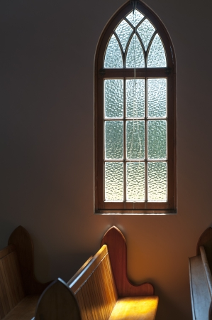 pew: sunlight through a window lights up a church pew  A simple place of worship showing a lead light window with the sun lightening up a simple pew Stock Photo