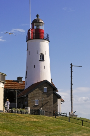 ijsselmeer: Lighthouse on the Ijsselmeer at Urk  on a blue sky day, the light house in the small fishing village of Urk on the Ijsselmeer in Holland Stock Photo