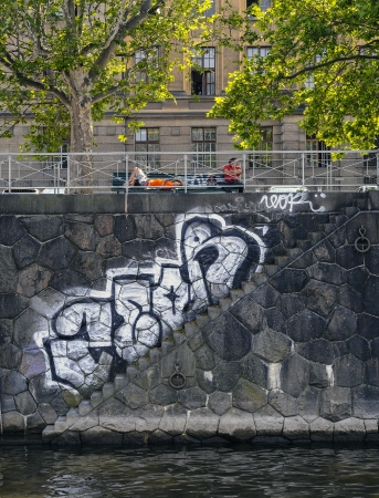 vandal: black and white graffiti on a block wall in Prague  On the banks of the Vlatava river, with a set of steps joining the adjacent road and footpath to waters edge and a place to tie a boat, the graffiti follows the steps