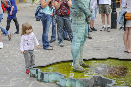 A little girl looks at the David Cerny  pissing  statue in Prague and no doubt ponders the mystery of life and anatomy
