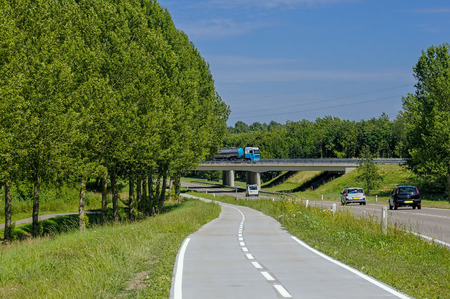 lelystad: roading and cycle paths in the Netherlands. This is near Lelystad showing modern roading, overbridge and safe cycle paths beside. A summer image with blue sky, green trees and mature trees