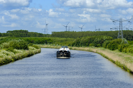 lelystad: The barge Eben Haezer sailing on the Lage Vaart, one of the canals near Lelystad. It is a summer day with the green park like surrounds . In the background can be seen wind powered turbine