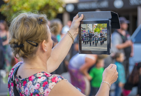 christma: A middle aged woman films a piper band in a christma street parade on a tablet device Editorial