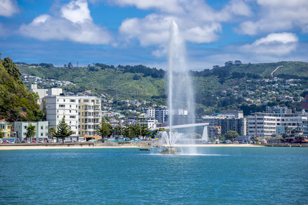 wellingtons: Wellingtons Oriental Bay on a blue sky day, showing the clear water of the bay, the luxurious and expensive apartment buildings, the green hills behind and sweeping around to the city CBD on the right, The fountain is sending water into the air. Editorial