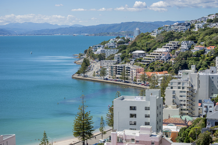 Wellington Harbour and Oriental bay on a fine sunny calm blue sky day showing the calm clear blue water, oriental bay beach, and the various high rise apartment buildings