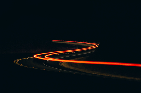 A cars taillights weave through a two-lane highway in Moccasin, California.