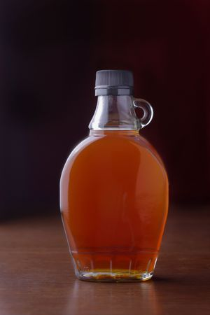 A bottle of maple syrup sits on a table Banco de Imagens