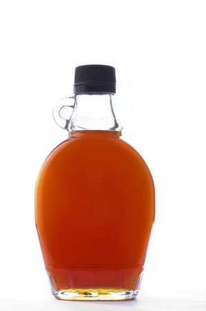 A bottle of maple syrup sits on a white background