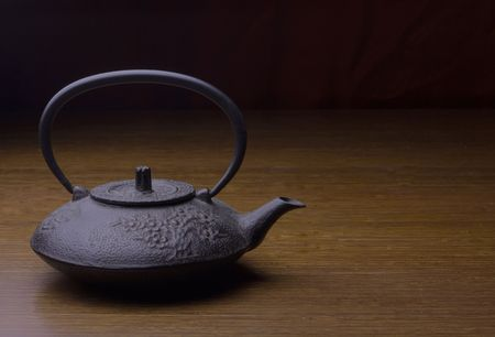 A cast-iron teapot sits on a table Stock Photo