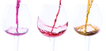 Three wine glasses are filled with different-coloured liquids