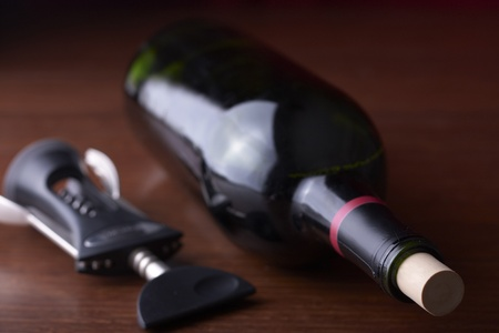 A wine bottle sits on a table with a corkscrew
