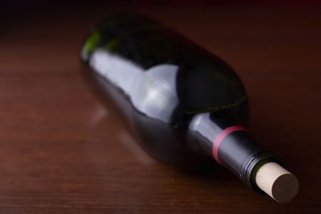 A wine bottle sits on a table Imagens