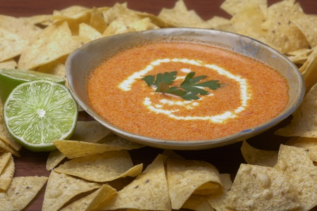 A bowl of soup sits among tortilla chips.