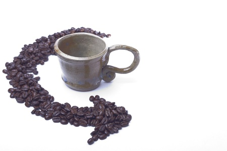 A cup sits on a white background with coffee beans arranged in arrow form