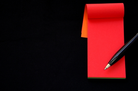 Red Note paper and pen isolated on black background Stock Photo - 13728368