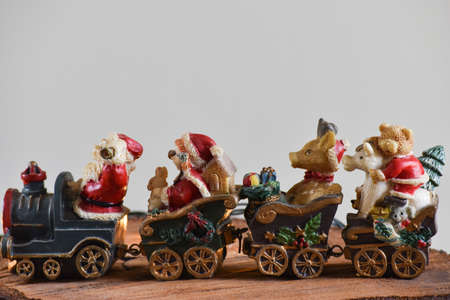 Christmas decoration: Santa's old sleigh with toys, reindeer, trees and stars on a rustic table with gray background. with space for text