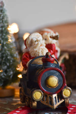 Christmas decoration: Santa's old sleigh with toys, reindeer, trees, stars and light on rustic table with gray background