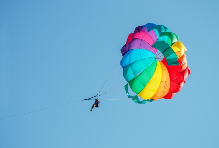 parasailing: One male parasailing on the blue sky