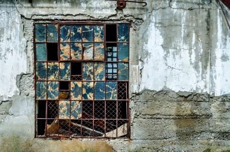 ventana rota: Vieja ventana rota en la pared de hormig�n gris