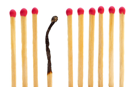 burnt out: Matches on a row with one burned Stock Photo