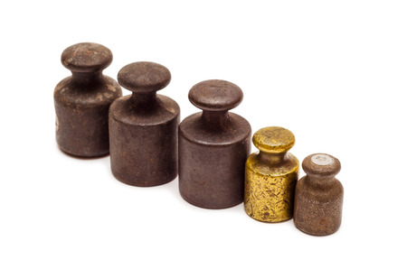 ponderous: Set of five antique calibration weights in row, one gold, isolated on white background