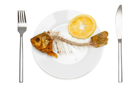 Fish skeleton with squeezed lemon on the plate - symbol for food shortage and misery.