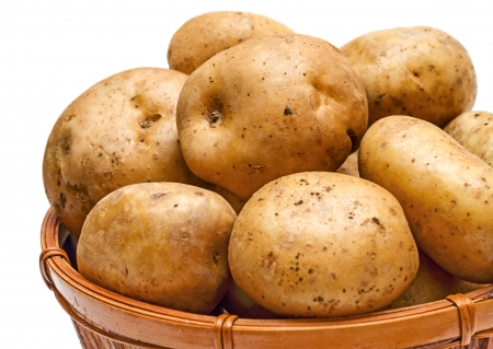 Yellow potatoes in the basket close-up isolated on white background photo