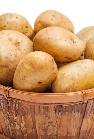 Potatoes in basket close-up isolated on white  photo