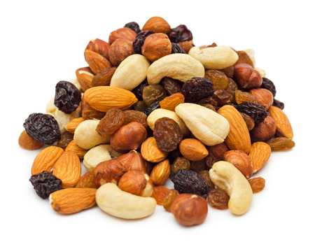Mixed nuts and dry fruits pile isolated on white background Stock Photo