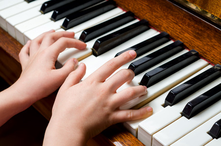 Llittle girl trying to play the piano with her little fingers. photo