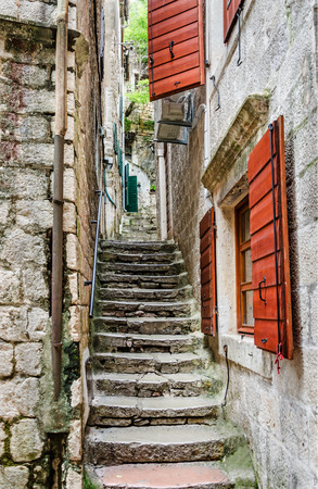 Old stone stairs through a narrow alley with red shutters in the old town of Kotor, one of the most famous places on Adriatic coast of Montenegro. photo