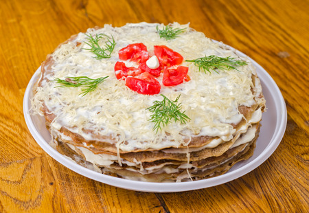Liver cake with garlic, dill sauce and tomatoes in the white plate on wooden table. photo