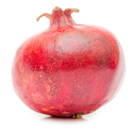 Whole ripe pomegranate isolated on white background.