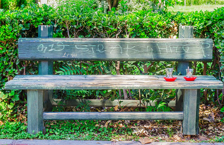 Empty Cups of tea on the outdoor wooden old green bench. Romance and weekend concept. Relaxation scene.