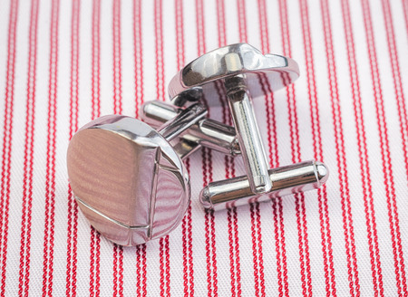 cuff: Silver cuff links on striped red background close up.