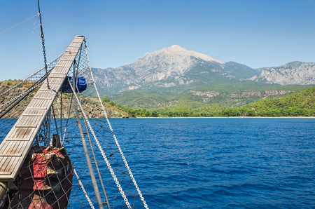 olympus: Wooden bowsprit of  an old sailing ship against the backdrop of the mountain Olympus (Tahtali Dagi), Turkey.