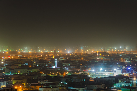 Light of old Dubai at night in fog.