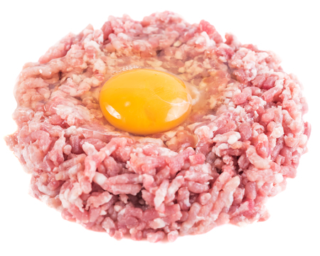 83cd9ed0ee674 Ground cutlet or raw hamburger with chicken egg yolk isolated on white  background. Close-