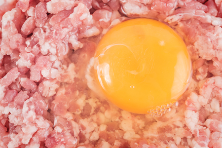 Ground cutlet or raw hamburger with chicken egg yolk isolated on white background. Close-up. Stock fotó