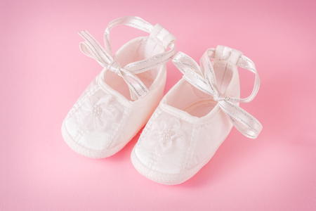 4aa9a6b7b3b12 White baby shoes on pink background. A pair of baby shoes. It`s a
