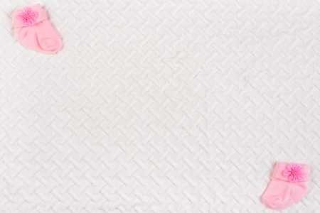 1128bcd4c4d5f Top view of baby socks for newborn on white blanket. Copy space for text.