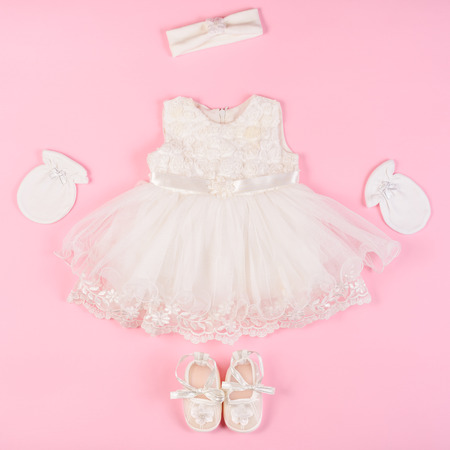 bff0e0dc3c48a Beautiful baby dress with booties and gloves isolated on a pink background