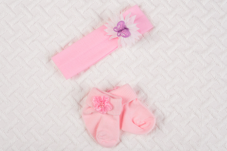 50b4aa17009ff Top view of baby socks and hair band for newborn on white blanket. Copy  space