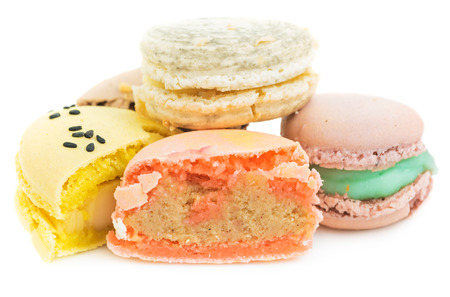 Pile of different types of french sweet cookies, macaroons cut in half. Isolated on white background.