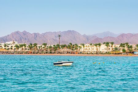Resort coast without people. An empty beach with many sun loungers and umbrellas. The concept of the collapse of the tourism industry. Red Sea near coast of Sharm El Sheikh city in Egypt.