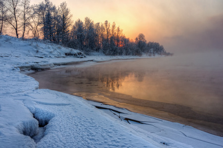 water's edge: river covered with snow and illuminated with light of the setting sun Stock Photo