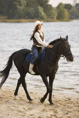 Woman ride the horse near water photo