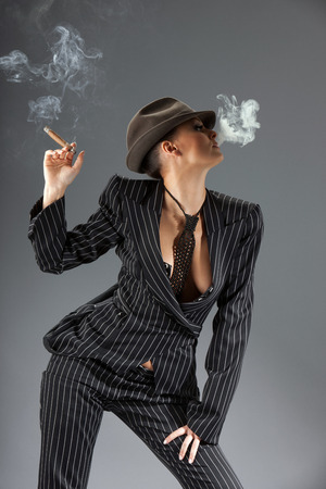 organized crime: Smoking gangster women over gray background