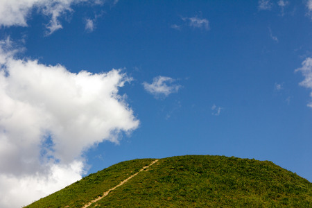 over the hill: footpath on top of a green hill against the blue sky